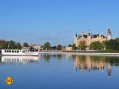 Ein Ausflugsschiff der Weissen Flotte vor dem imposanten Schloss von Schwerin. (Foto: Schwerin Tourismus)