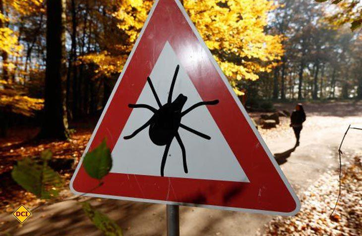 Achtung Zecken – Warnschild auf einem Wald-Wanderweg. (Foto: Pfizer)