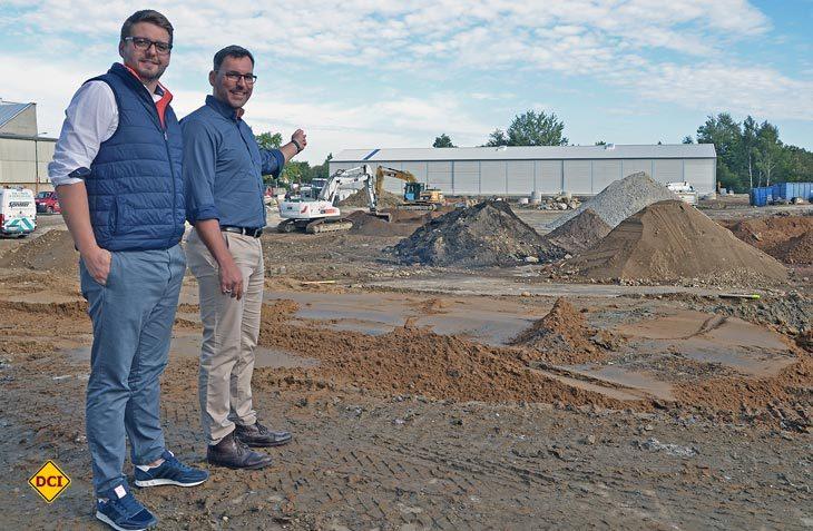 Capron-Geschäftsführer Daniel Rogalski (re.) und Projektleiter Toni Pietsch (li.) vor der Baustelle der neuen Fertigungsstätte. Schon bald wird hier die neue 10.000 Quadratmeter große Produktionshalle entstehen. (Foto: Capron GmbH, F. Kramer)