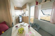 Blick von der Hecksitzgruppe auf Küche, Sanitärraum und Bugbett des c´joy 410 QL von Dethleffs. (Foto: Werk)