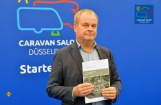 """Dirk Dunkelberg, Stellvertretender DTV-Hauptgeschäftsführer. hat die neue Planungshilfe """"Reisemobilstellplätze in Deutschland"""" auf dem Caravan Salon 2018 in Düsseldorf vorgestellt. (Foto: det)"""