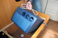 Jetzt wird das Gerät an den für die Sicherung vormontierten Spanngurten probehalber in den Sitzstaukasten versenkt und der korrekte Sitz der Aussparungen kontrolliert. (Foto: has)