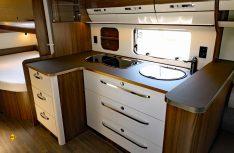 Viel Arbeitsfläche und Stauraum bietet der winkelförmige Küchenblock. (Foto: sis / D.C.I.)