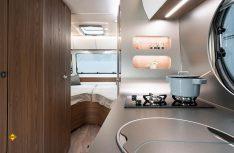 Blick auf die großzügige Küche und der komfortable Schlafraum mit dem V-Heckbett. (Foto: Werk)