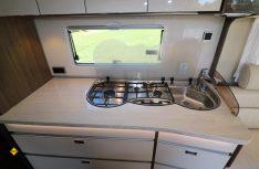 Formschöne Küche mit hochglänzenden hellen Fronten und klappbarer Zusatzplatte. (Foto: sis / D.C.I.)