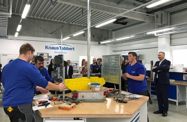 Geschäftsführer Werner Vaterl (r.) und die Ehrengäste sehen den Elektroniker-Azubis bei der Arbeit zu. (Foto: Knaus Tabbert)