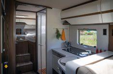 Blick auf die üppige Küchenzeile und den abtrennbaren Schlafbereich mit komfortablen Einzelbetten. (Foto: Hymer)